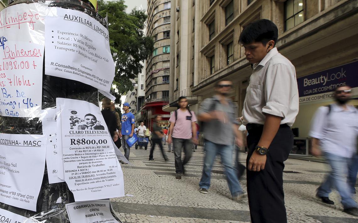 Homem olha anúncios de vagas no centro de São Paulo