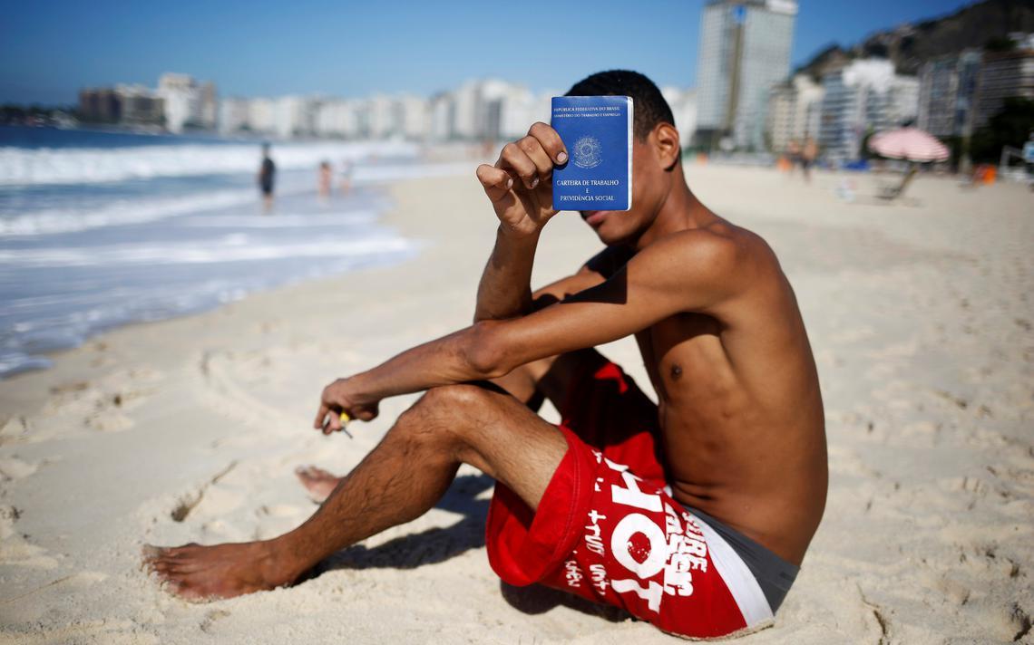 Jovem desempregado mostra sua carteira de trabalho em Copacabana