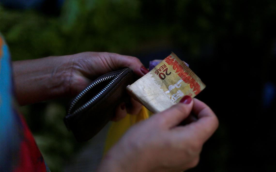 Mulher tira suas notas da carteira para comprar em feira livre