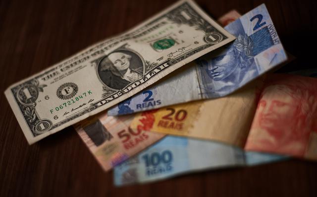 Nota de um dólar sobre quatro notas de real, jogadas em uma mesa. Nas notas de real, há uma de 2, uma de 20, uma de 50 e outra de 100 reais.