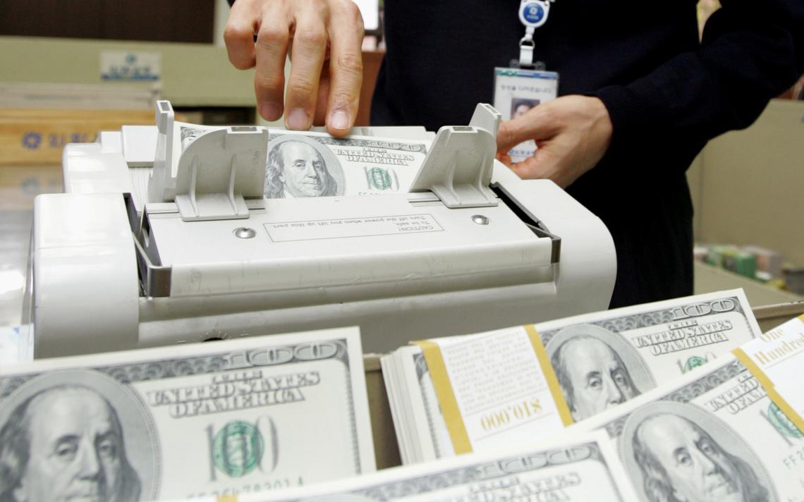 Funcionário de casa de câmbio conta dólares