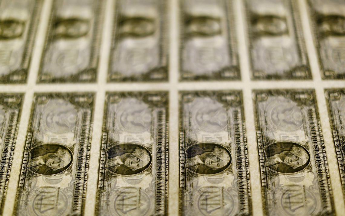 Notas de dólar durante processo de impressão e gravação em Washington