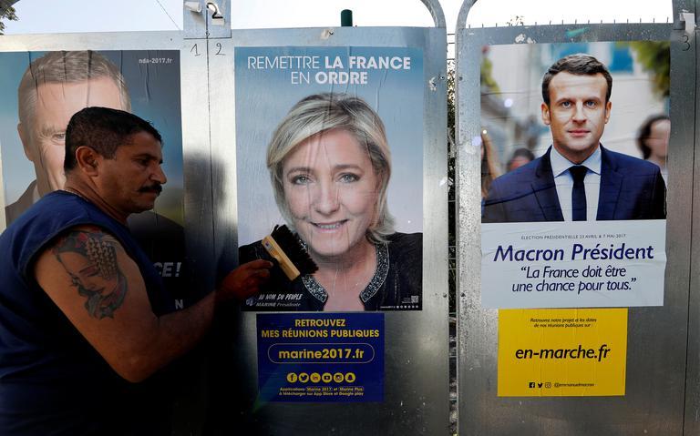 Homem caminha em frente a cartazes de Le Pen e Macron