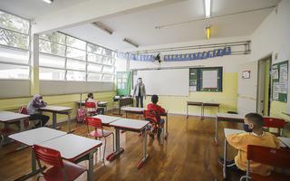 Imagem mostra sala de aula com apenas quatro estudantes, de máscara, sentados distantes uns dos outros; professora está em pé, na frente do quadro branco, usando máscara e face shield