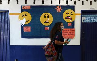 Imagem mostra menina com mochila e máscara, segurando uma garrafa de água e o celular, caminhando em frente a um mural com desenho de 3 bonequinhos com termômetro na boca, lenço no nariz e gotículas saindo da boca para conscientizar sobre a covid-19