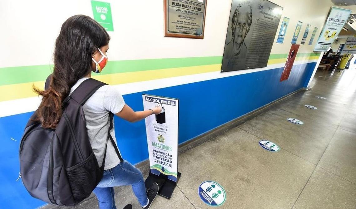 Menina com mochila nas costas dispara com o pé dispositivo que libera álcool em gel nas mãos. Equipamento está instalado em correr de escola estadual no Amazonas