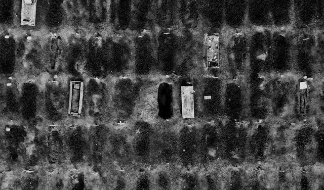 Foto aérea de covas no cemitério. Ao centro, uma cova aberta. Em volta dela, covas já fechadas