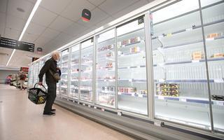 Homem idoso olha para geladeiras quase vazias em supermercado