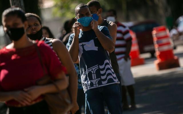 Em fila, pessoas desfocadas usam todas máscaras. Homem em destaque ajeita máscara