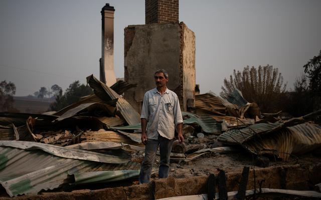 Um homem, olhando para o lado, está em pé em meio a telhas, pedaços de madeira e escombros.