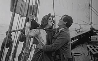 Em barco, casal se beija. Ela se agarra a cordas presas a embarcação