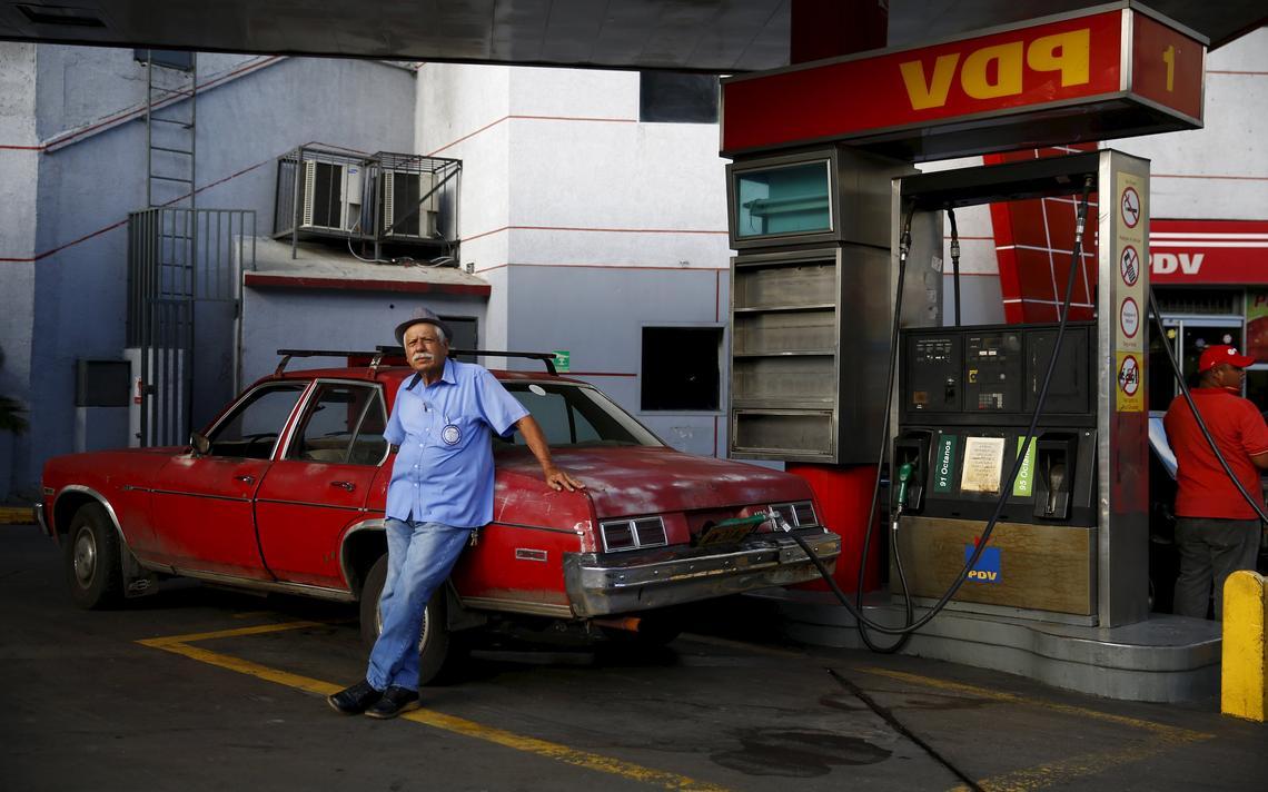 Homem abastece o carro em Caracas
