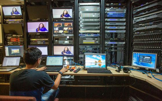 Bastidores de um estúdio de TV com várias televisões, e um homem trabalhando num computador
