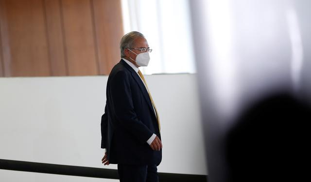 Paulo Guedes desce rampa, de máscara