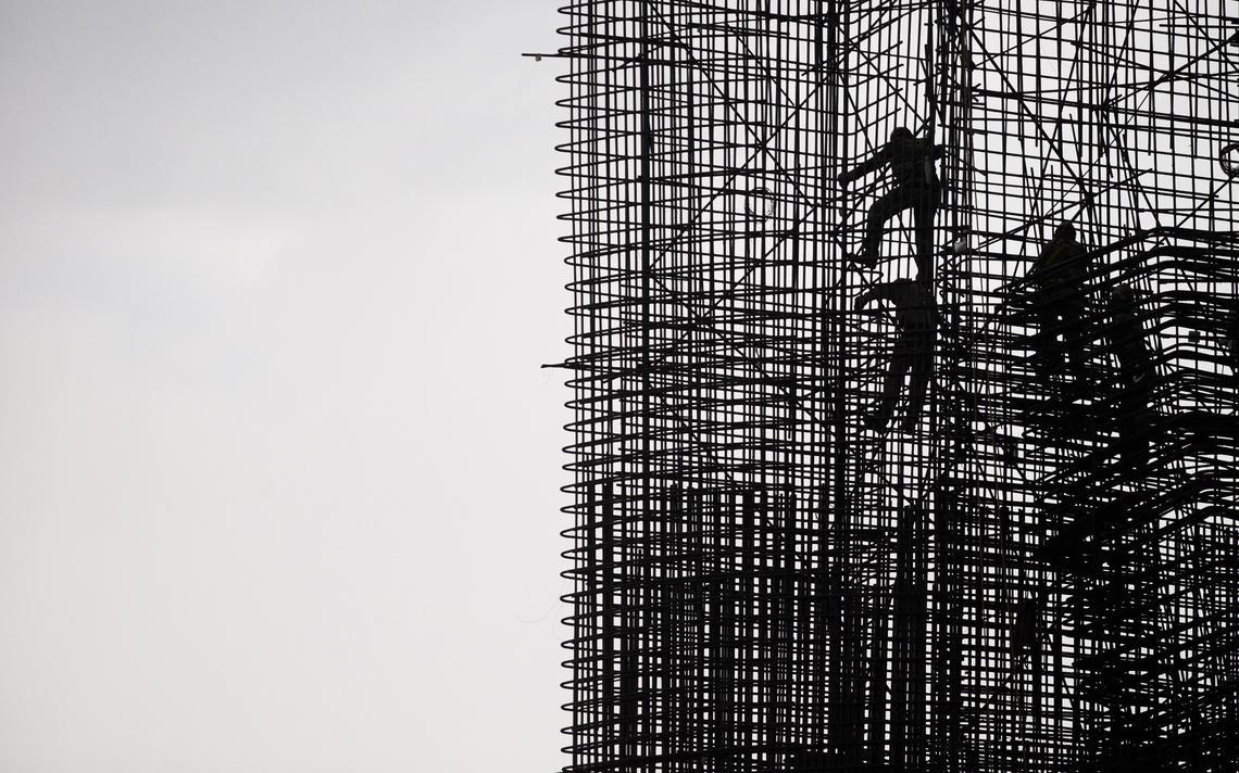 Trabalhadores sobem em estrutura metálica durante construção de hidrelétrica