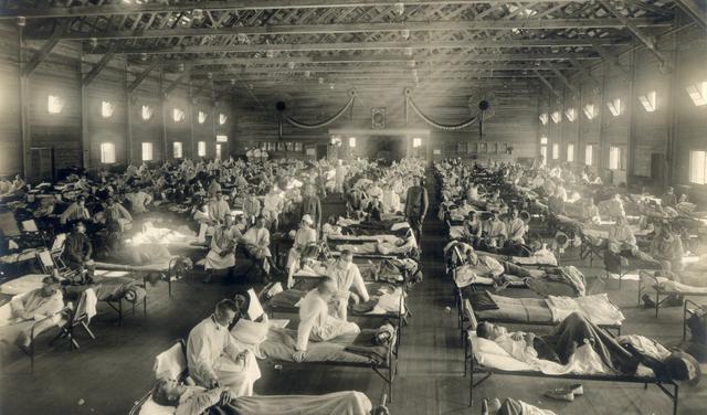 Hospital de campanha no Kansas, nos EUA, durante a pandemia da gripe espanhola. Várias fileiras de camas estão estendidas com pessoas deitadas. Médicos são vistos perto das camas usando máscaras.