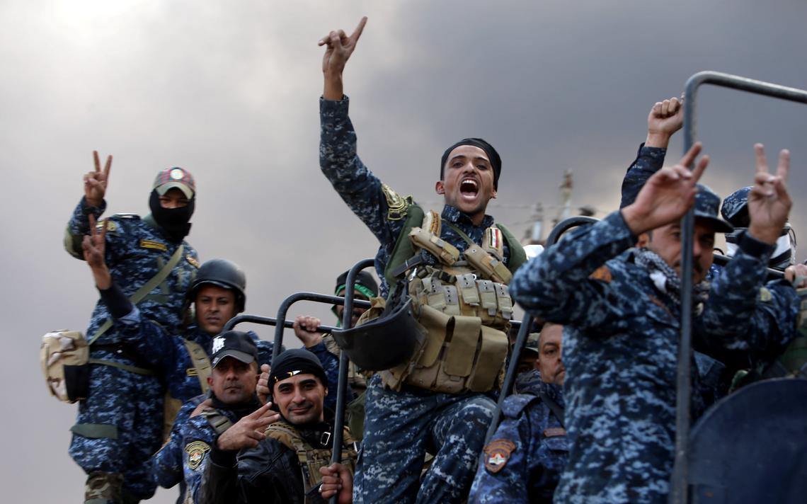 Combatentes acenam para foto em Qayyarah