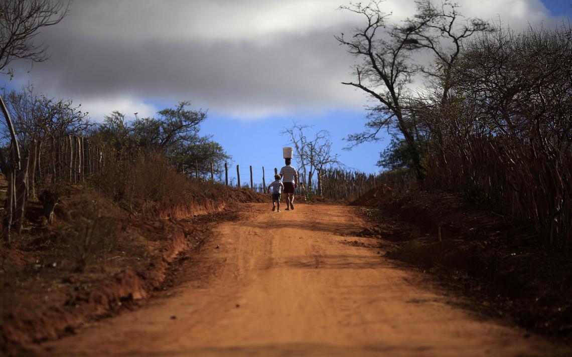 Homem carrega balde de água ao lado de seu filho na comunidade Fumaça, na Bahia, em 2012.