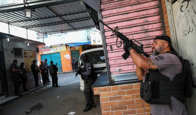Homem com camiseta cinza e colete a prova de balas preto aponta fuzil para cima. Ele está encostado em uma mureta de tijolos com uma porta de ferro em cima. Ao fundo, se veem outros policiais com armas