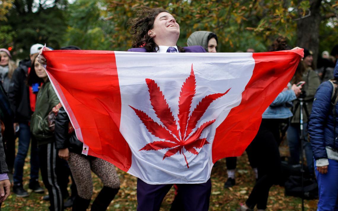 Jovem estende bandeira do Canadá com a representação da folha de cannabis, no parque Trinity Bellwoods, em Toronto