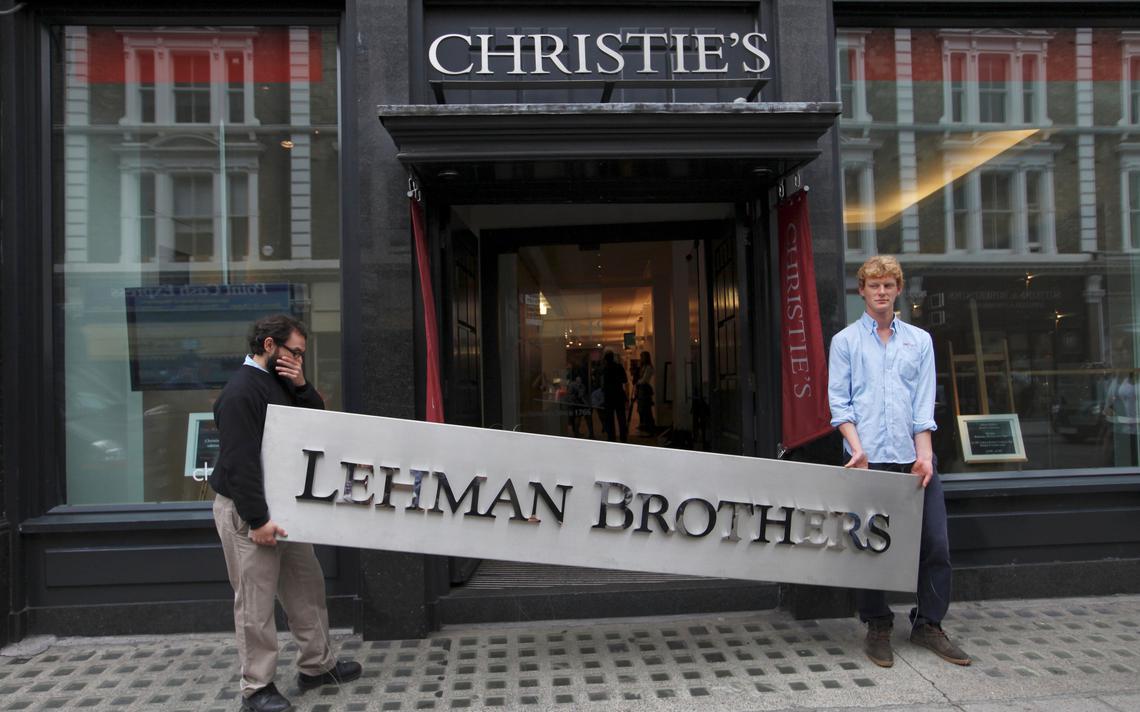Funcionários da casa de leilões Christie's seguram placa do Lehman Brothers prestes a ser vendida em Londres