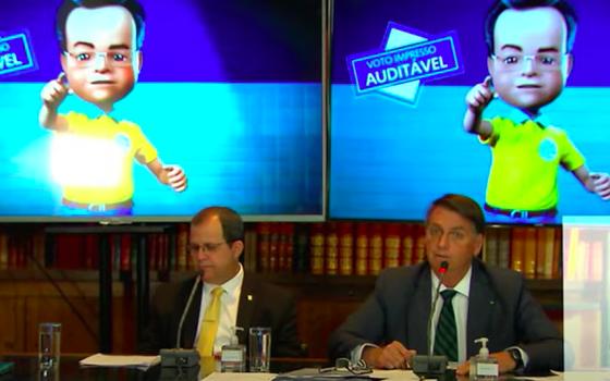 """Gomes e Bolsonaro, sentados à mesa. Ao fundo, telões exibem boneco com os dizeres """"voto impresso auditável"""""""