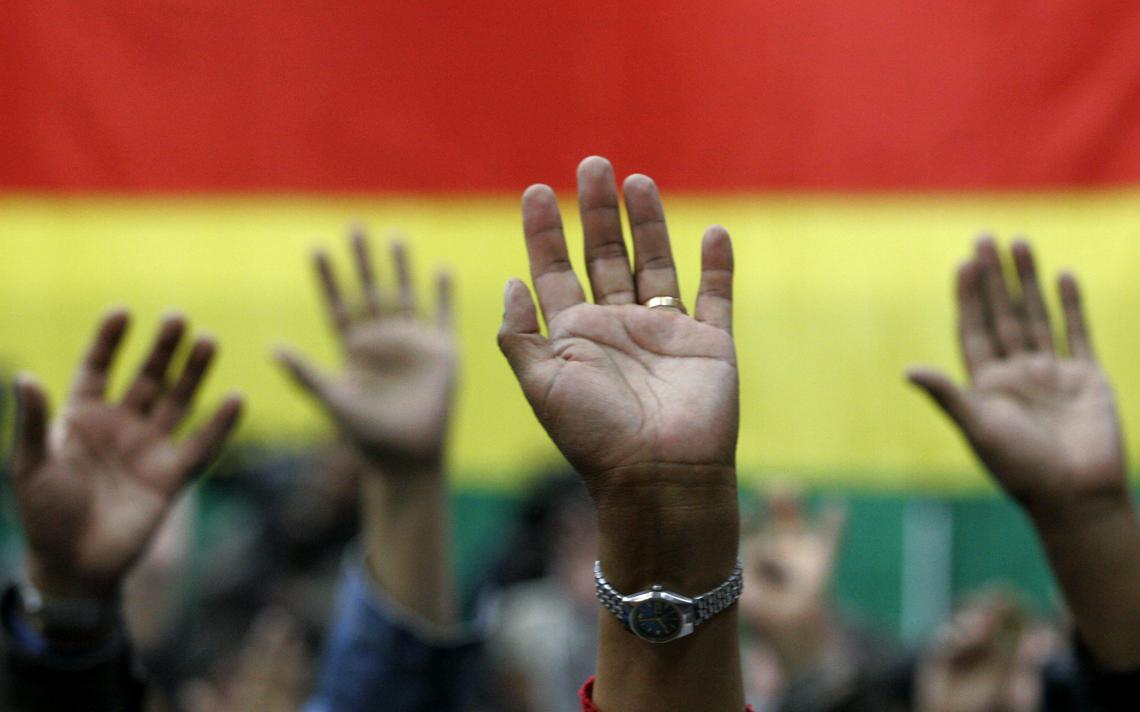 Pessoas levantam as mãos em votação