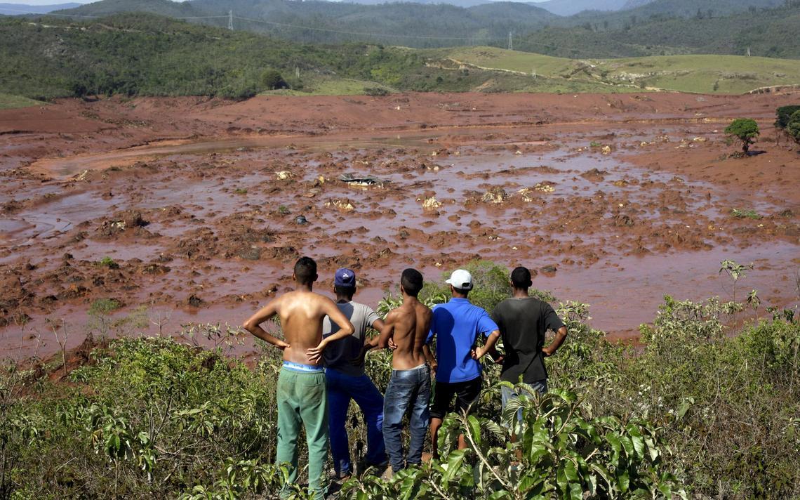 Homens olham para cidade devastada pela lama