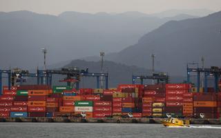 Vista de containers esperando embarque no porto de Santos. Em primeiro plano, no mar, há um barco amarelo. Ao fundo, serra do Mar