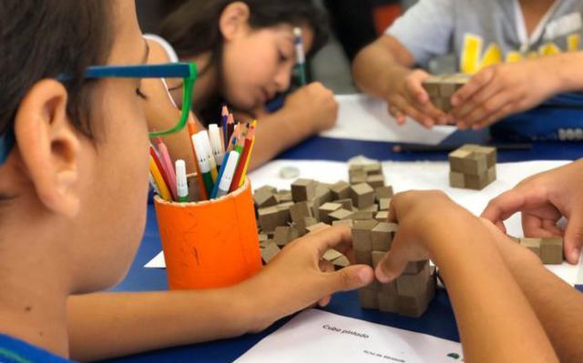 De costas, vê-se um menino brincando com blocos de madeira sobre a mesa. Há outras três crianças com ele brincando e escrevendo.