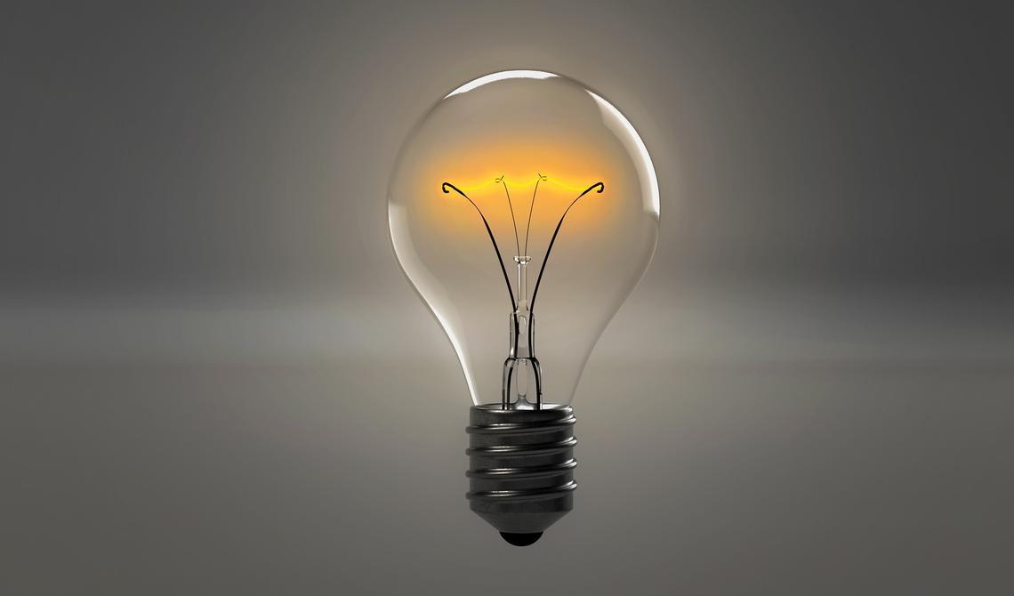 Uma lâmpada acesa em um fundo cinza