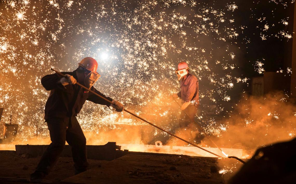 Homens trabalham em siderúrgica na província de Shandong, na China