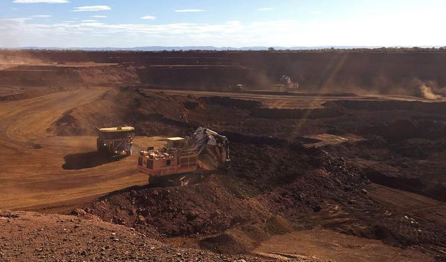 Uma escavadeira opera sobre uma montanha de terra que parece ferrugem. Ao fundo, toda a área está desmatada e com a terra seca exposta