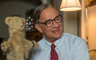 Homem com óculos e gravata vermelha sorri para fora do quadro. Na mão direita, ele segura um fantoche de leão com braços abertos
