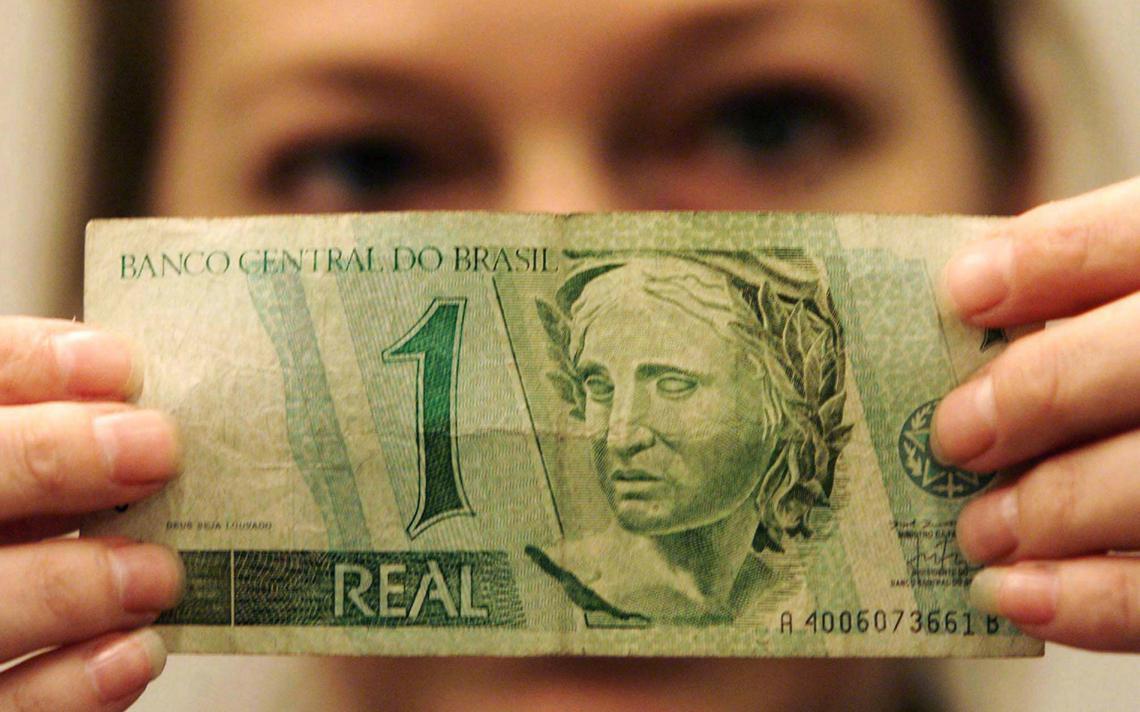 Mulher segura nota de R$ 1