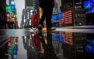 Pessoa anda com carrinho de compras no Times Square vazio, em Nova York. Só se vê as pernas da pessoa, que está de calça e pisa evitando uma poça. A poça reflete as pernas da pessoa e os paineis eletrônicos do Times Square. Um deles, o que mais ocupa espaço na imagem, mostra uma bandeira dos Estados Unidos