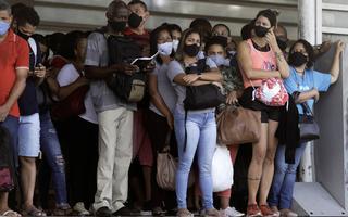 Aglomeração de pessoas em pé, muito próximas umas das outras, usando máscaras. Uma mulher olha para a câmera.