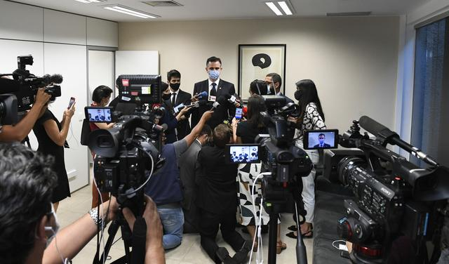 Em primeiro plano, repórteres seguram câmeras e microfones. Ao fundo, Rodrigo Pacheco