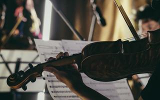 Violinista toca em frente à estante e partitura