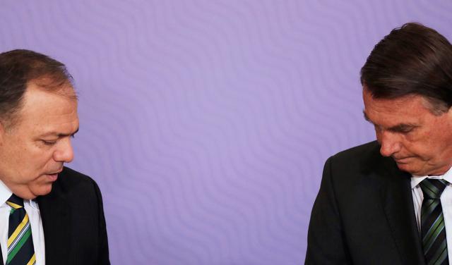 Imagem mostra o ministro Pazuello e o presidente Bolsonaro sentados, cada um numa ponta da foto, de terno, e ambos olham para baixo; o fundo é uma parede roxa