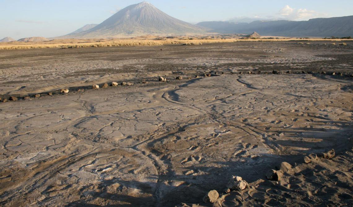 Com vulcão atrás, em primeiro plano, é possível ver uma série de pegadas no chão