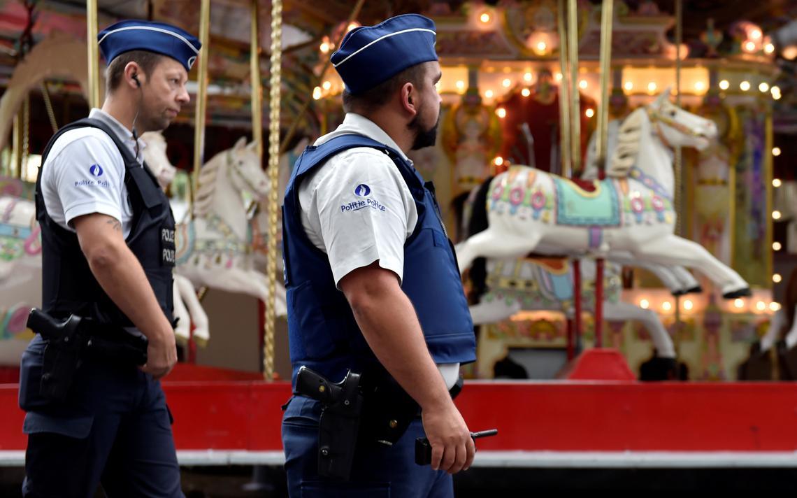 Policiais belgas passam em frente a carrossel durante feira