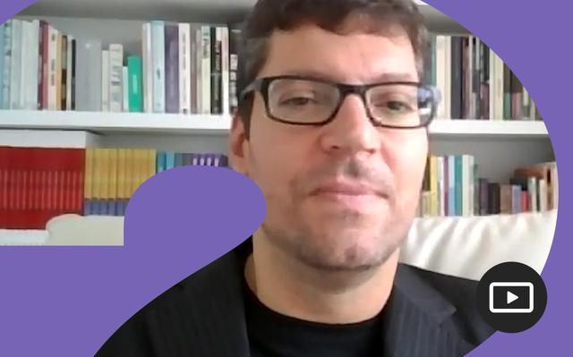 Rodrigo Hübner Mendes em entrevista feita em vídeo. Em volta da foto, há uma moldura roxa.