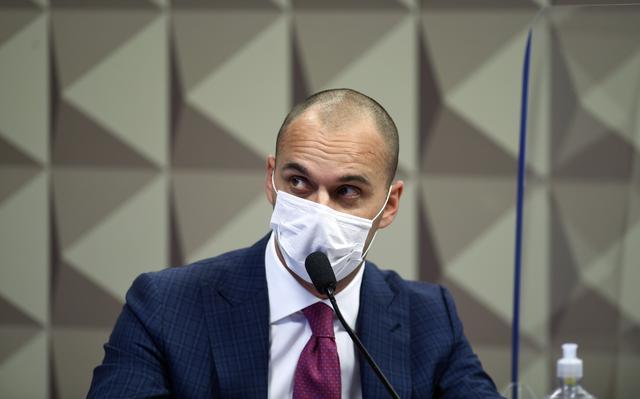 Imagem mostra o diretor da Prevent Senior, Pedro Batista Jr, de terno azul, gravata vermelha e máscara branca, sentado à mesa, falando ao microfone e olhando para seu lado direito