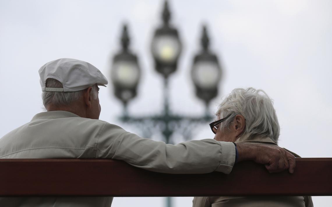 Casal de idosos sentado em banco de praça