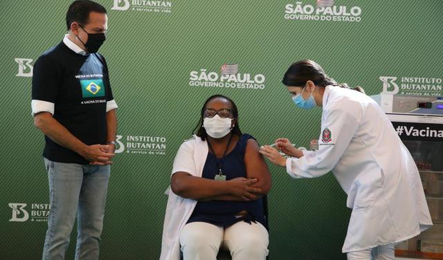 João Doria está em pé, ao lado de Mônica, sentada, que recebe uma vacina de uma mulher em pé