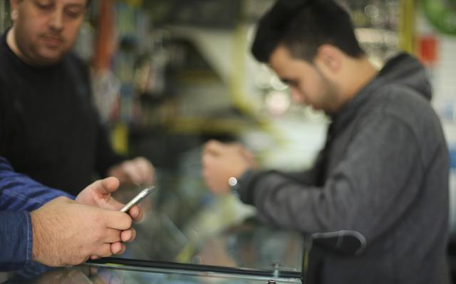Homens checam seus celulares