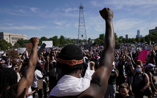 Em primeiro plano, homens negros de costas erguem o braço com punho fechado diante de manifestação