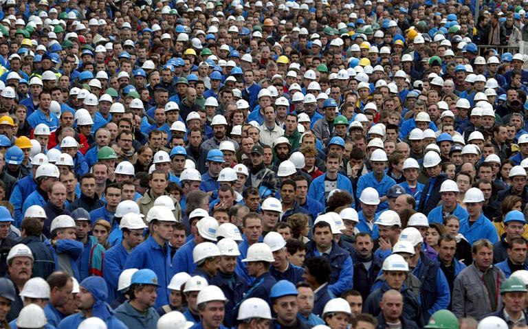 Trabalhadores se reúnem em pátio de fábrica