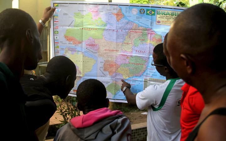 Haitianos refugiados estudam mapa do Brasil no Acre